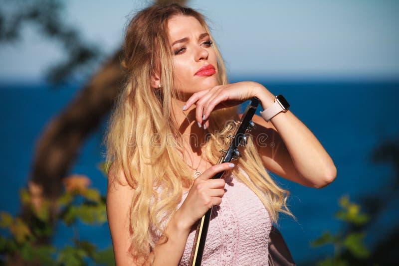 Donna bionda con la chitarra acustica sulla spiaggia fotografia stock libera da diritti