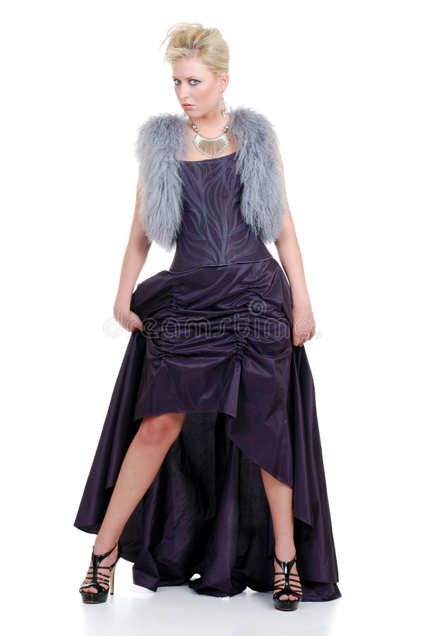 Donna bionda con la posizione viola della maglia e del vestito della pelliccia fotografie stock libere da diritti