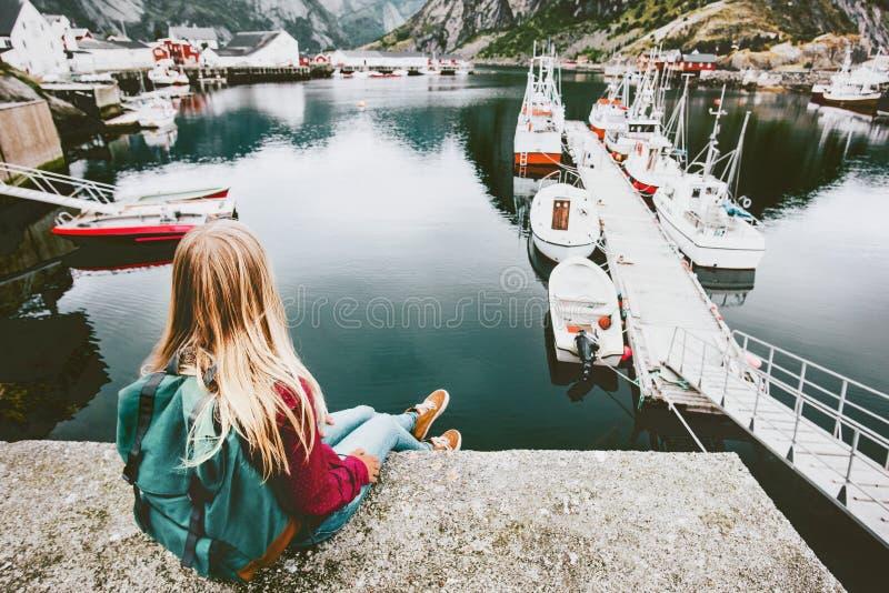 Donna bionda con lo zaino che si rilassa sul ponte sopra il mare immagini stock