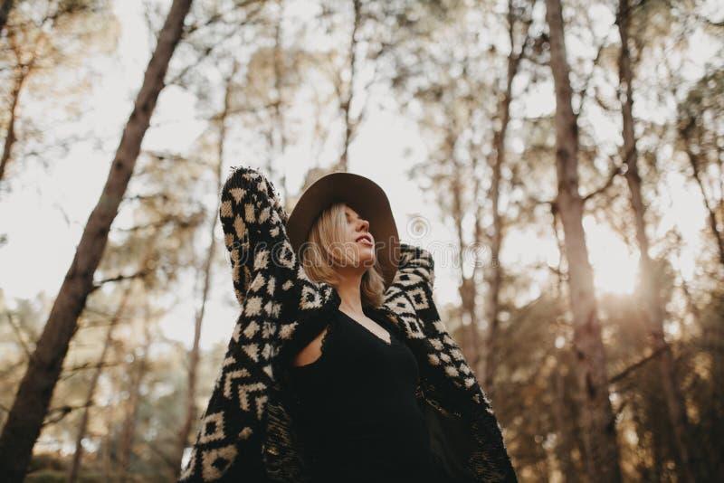 Donna bionda con un cappello che cerca nella campagna Alberi forestali nei precedenti immagine stock libera da diritti