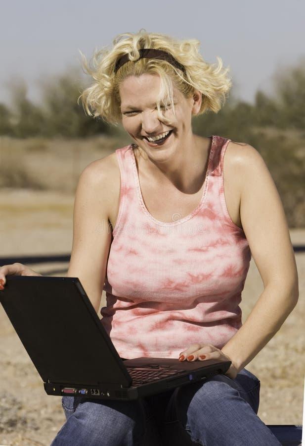 Donna bionda con un computer portatile fotografia stock