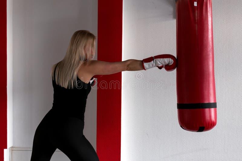 Donna bionda concentrata in guantoni da pugile rossi in abiti sportivi neri che fanno addestramento d'inscatolamento con un punch fotografia stock libera da diritti