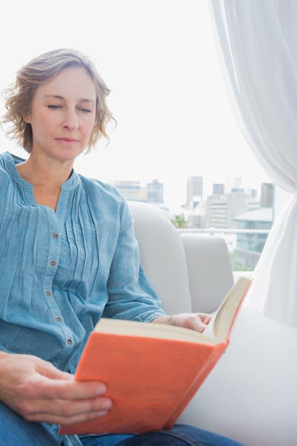 Donna bionda contenta che si siede sul suo strato che legge un libro immagine stock libera da diritti