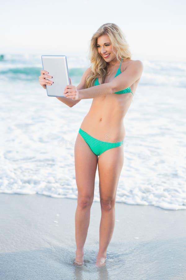 Donna bionda contentissima in bikini verde che tiene un pc della compressa immagine stock