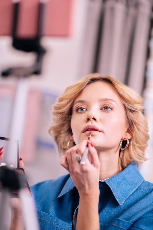 donna Bionda-dai capelli che colora le sue labbra mentre facendo il blog di bellezza immagine stock libera da diritti