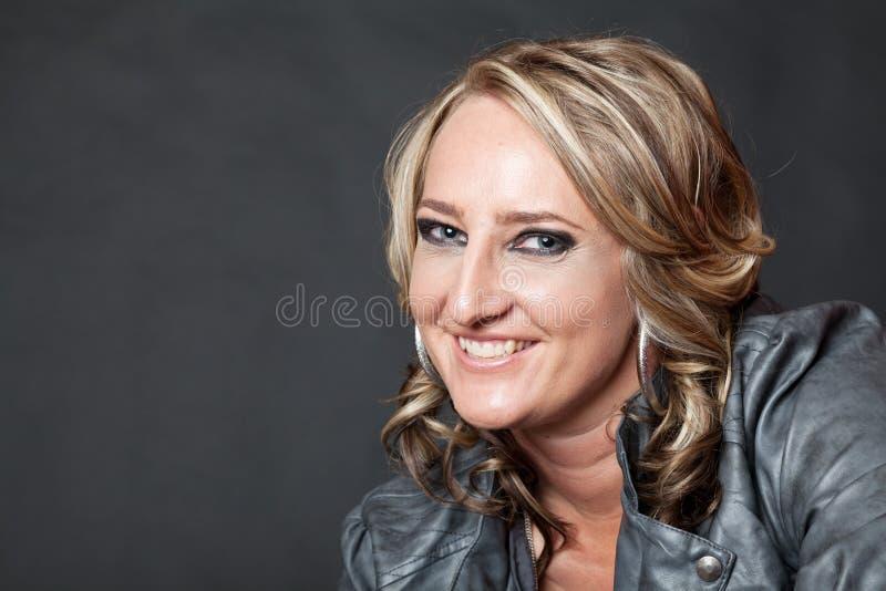 Donna bionda dai capelli riccia in studio, fondo grigio fotografie stock
