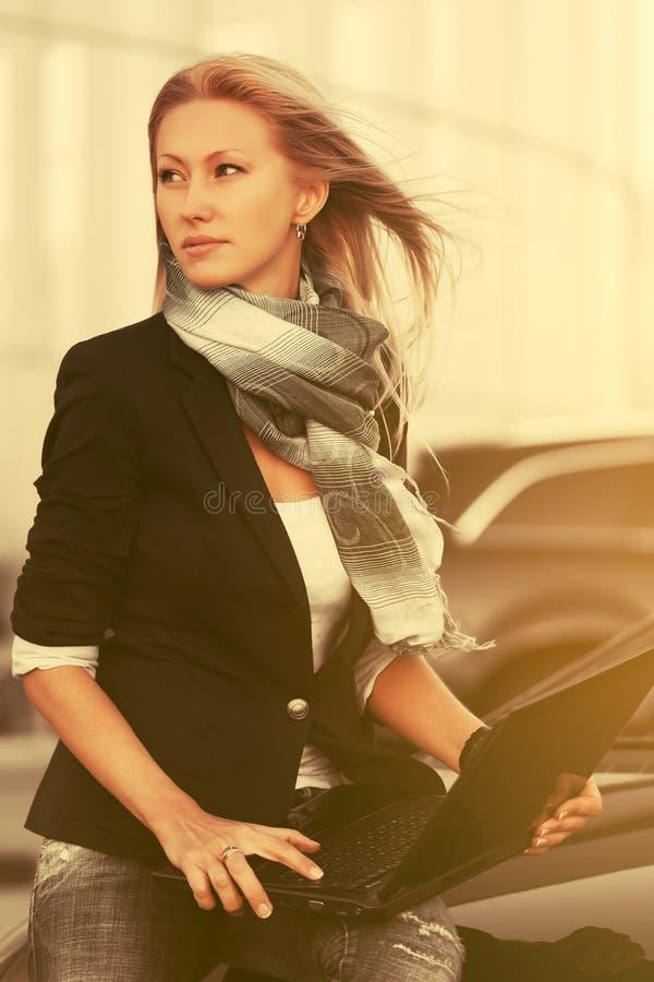 Donna bionda di affari di giovane modo con il computer portatile che si siede sulla sua automobile fotografie stock libere da diritti