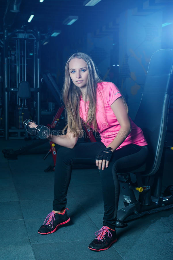 Donna bionda di forma fisica in abiti sportivi con l'ente perfetto che posa nella palestra Ragazza sportiva attraente che riposa  immagini stock