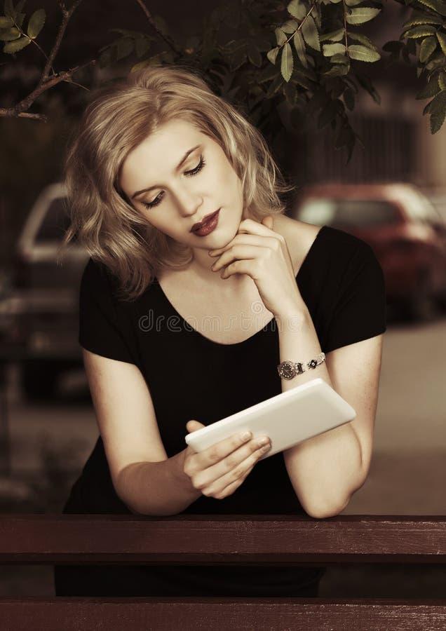 Donna bionda di giovane modo che utilizza il computer digitale della compressa nella via della città immagini stock libere da diritti