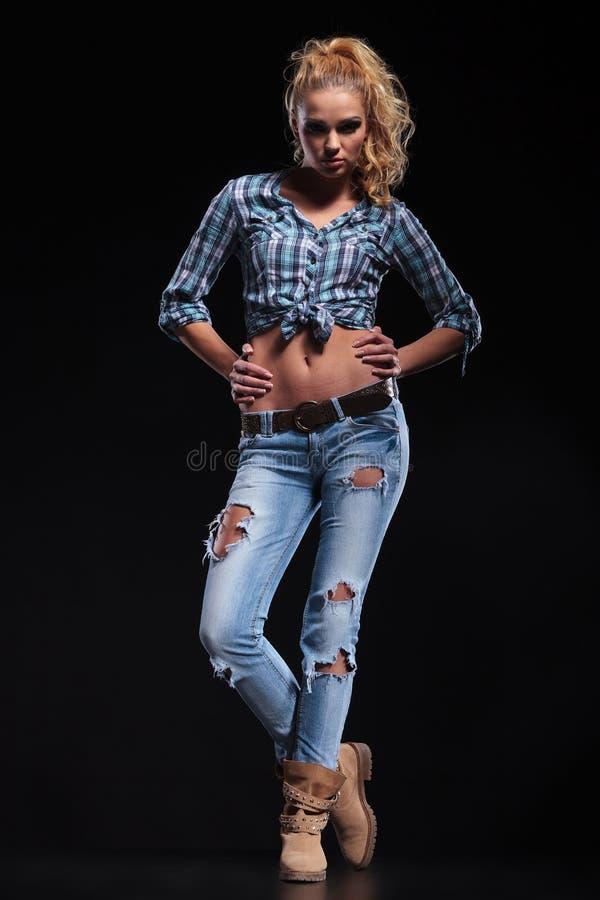 Donna bionda di giovane modo con le mani sulle anche fotografia stock