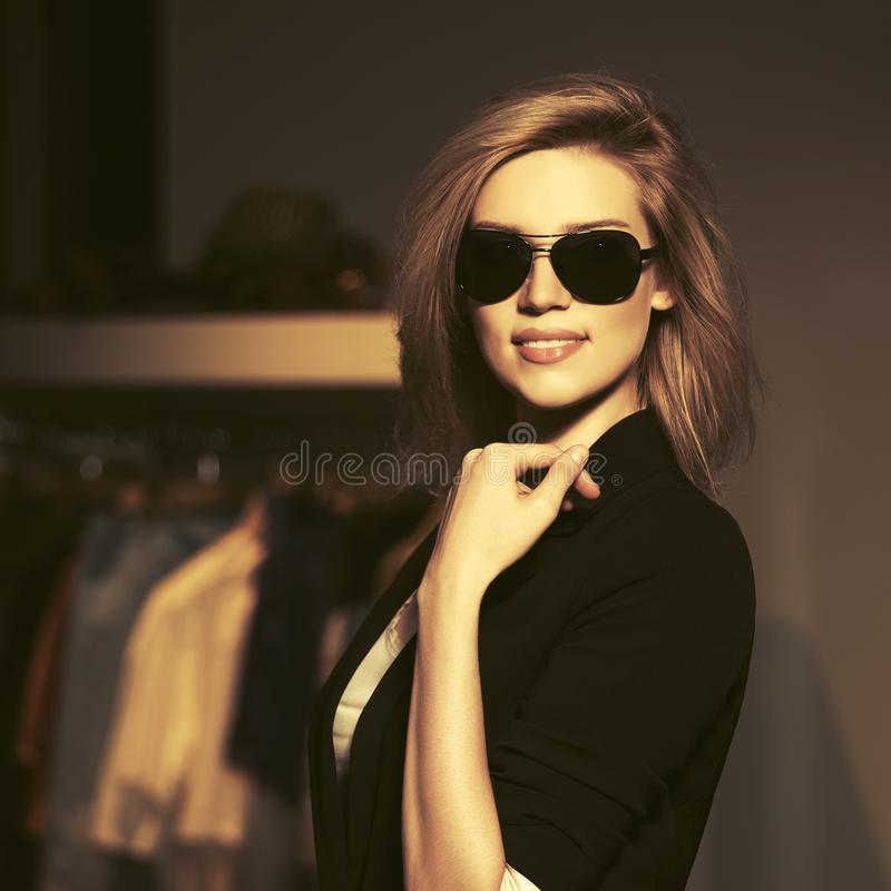 Donna bionda di giovane modo in occhiali da sole nell'interno del centro commerciale fotografia stock