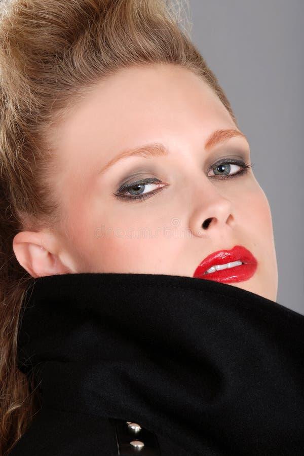 Donna bionda di Headshot con il cappotto nero fotografia stock