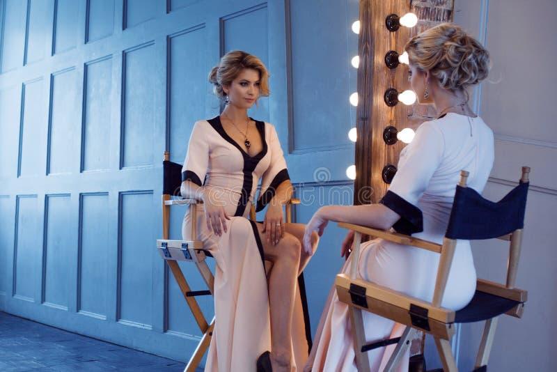 Donna bionda di lusso di bellezza Giovane modello attraente in bello vestito che si siede davanti allo specchio, per vestiresi el fotografia stock