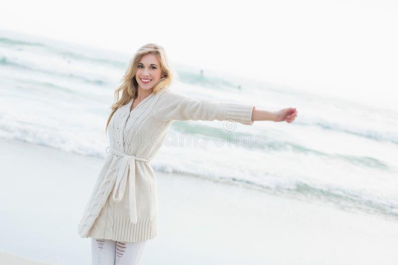 Donna bionda divertente nel cardigan della lana che la allunga armi immagine stock