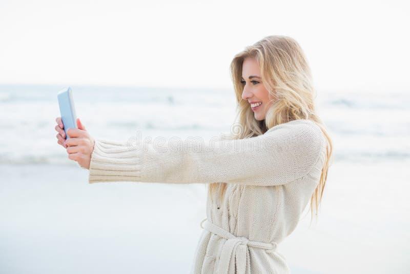 Donna bionda divertente nel cardigan della lana che prende un'immagine se stessa con un pc della compressa fotografie stock libere da diritti