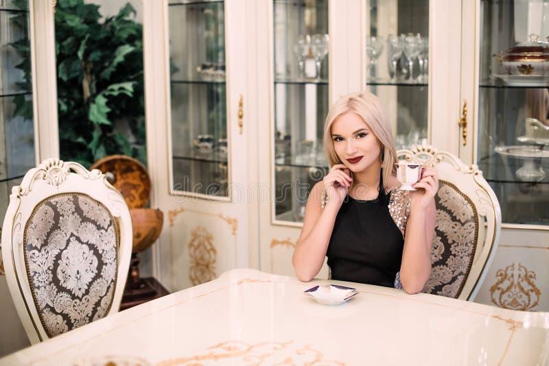 Donna bionda elegante alla moda nell'interno ricco di bellezza, vestito nero d'uso fotografia stock libera da diritti