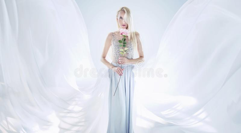 Donna bionda elegante che tiene un fiore rosa lungo immagini stock