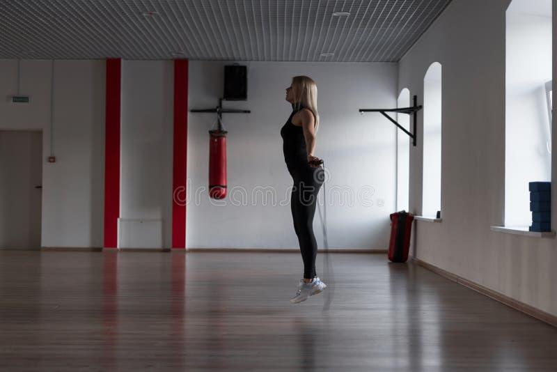 Donna bionda esile giovane che fa gli esercizi con un salto della corda in una palestra Ragazza di sport in un salto Cardio addes fotografia stock