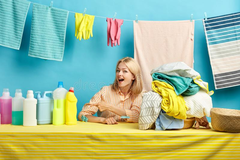 Donna bionda felice allegra in camicia a strisce che mostra lavando liquido in bottiglie fotografie stock libere da diritti