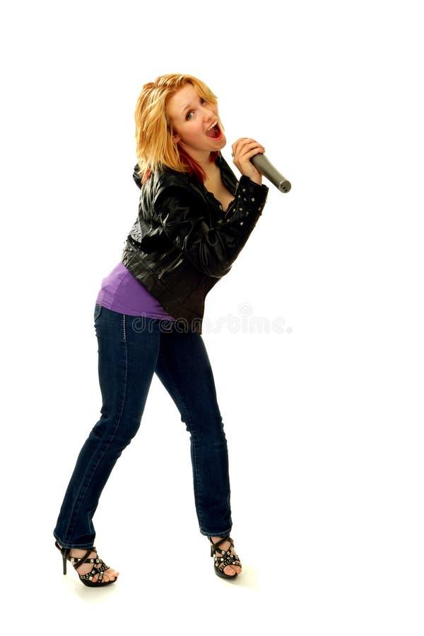 Donna bionda felice che canta con il microfono immagine stock