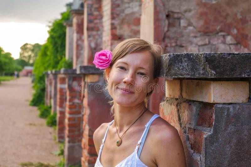 Donna bionda felice con il fiore rosa in suoi capelli che stanno davanti al muro di mattoni sul modo del parco immagine stock