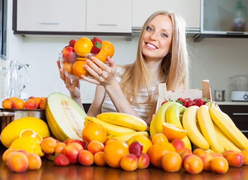 Donna bionda felice con il mucchio di vari frutti fotografie stock