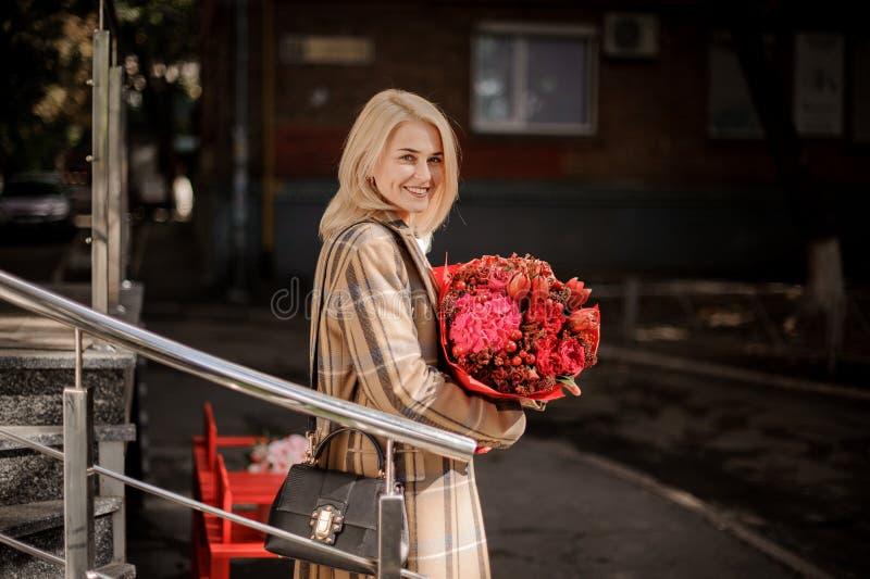 Donna bionda felice e sorridente in cappotto del plaid con un grande mazzo rosso dei fiori immagini stock libere da diritti