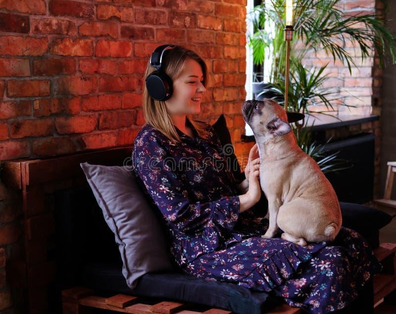 Donna bionda felice in vestito che gioca con il suo carlino sveglio e che ascolta la musica nella sala con l'interno del sottotet immagine stock libera da diritti