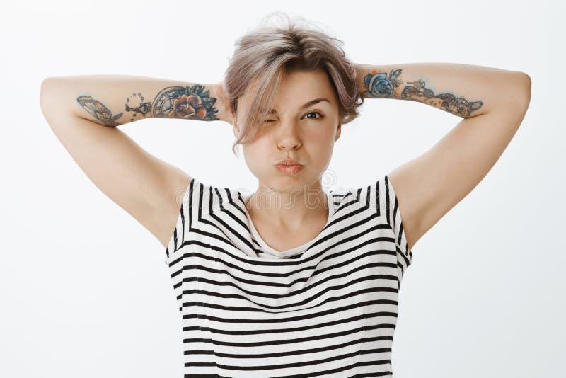 Donna bionda femminile sicura con i braccia tatuati, sporgendo le labbra, pettinando capelli dietro con le mani, rendenti civettu fotografia stock libera da diritti