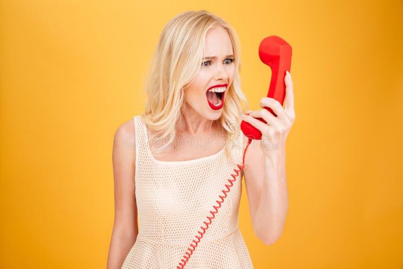 Donna bionda giovane arrabbiata di grido che parla per telefono fotografie stock libere da diritti