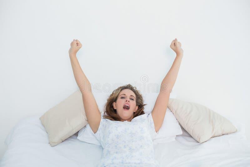 Donna bionda graziosa che allunga a letto e che sbadiglia immagini stock libere da diritti