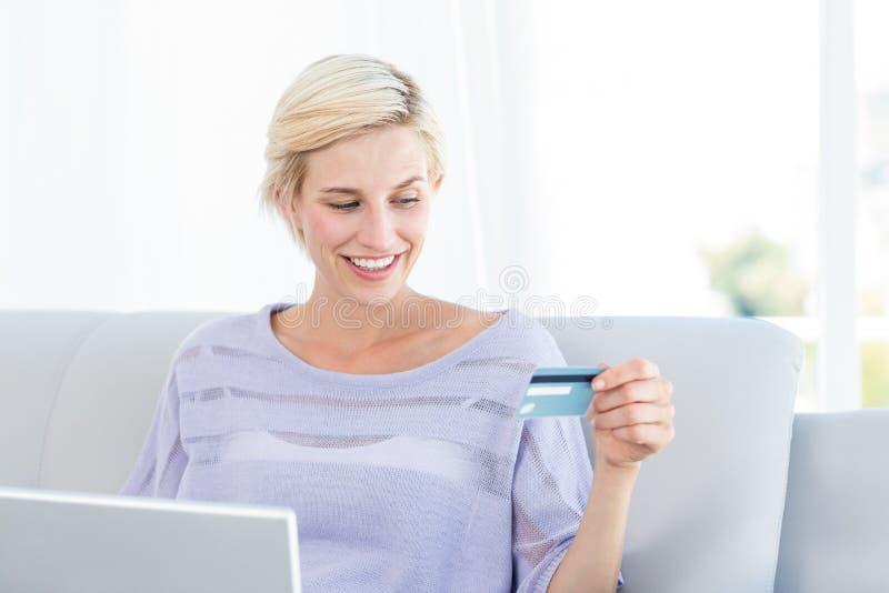 Donna bionda graziosa che fa spesa online fotografia stock