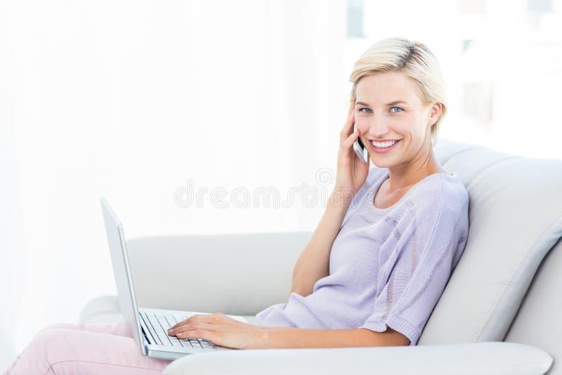 Donna bionda graziosa che rivolge al telefono e che per mezzo del suo computer portatile immagini stock