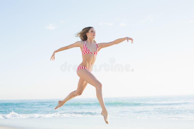 Donna bionda graziosa che salta sulla spiaggia fotografia stock libera da diritti