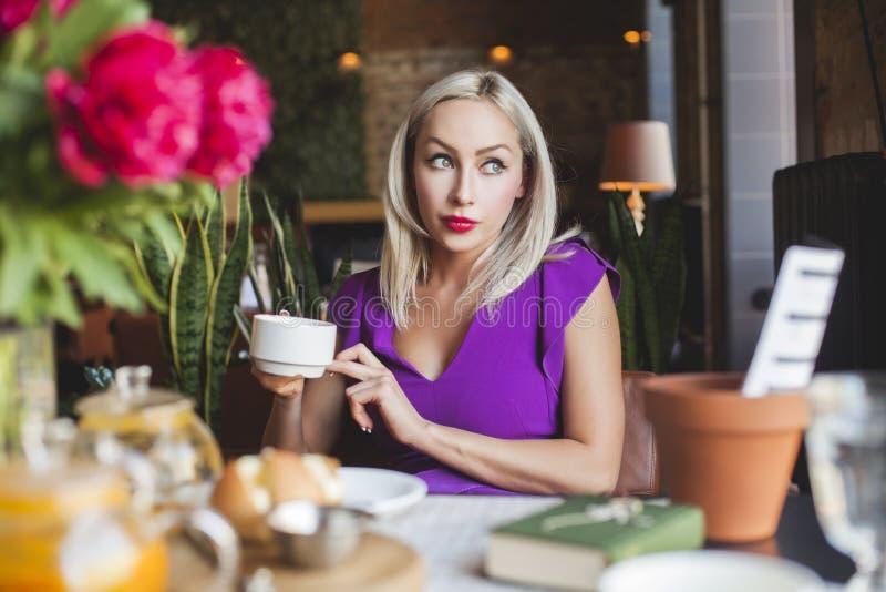 Donna bionda graziosa che si siede in caffè immagine stock libera da diritti