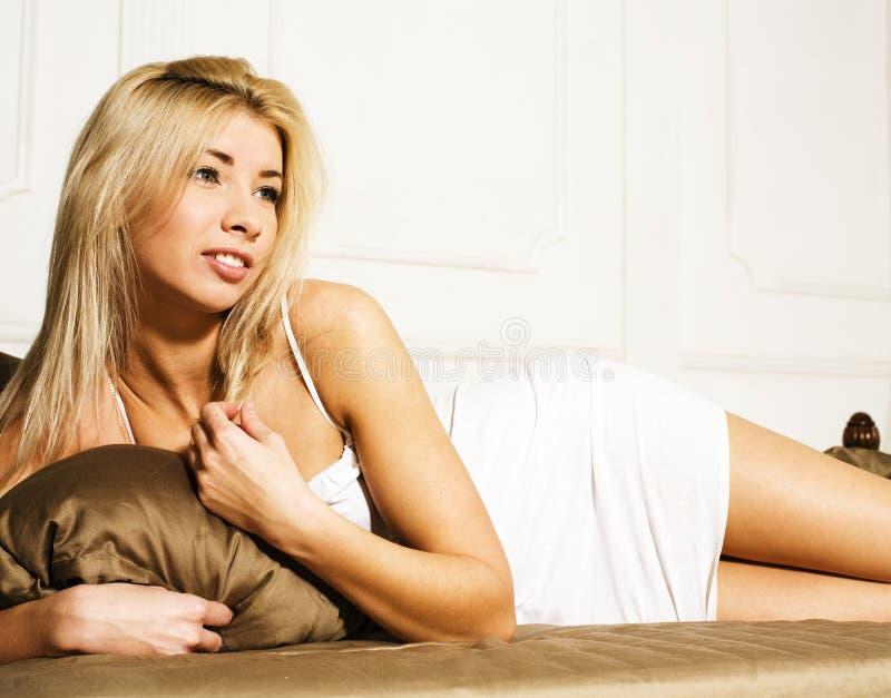 Donna bionda graziosa che si situa a letto, biancheria sensuale fotografia stock