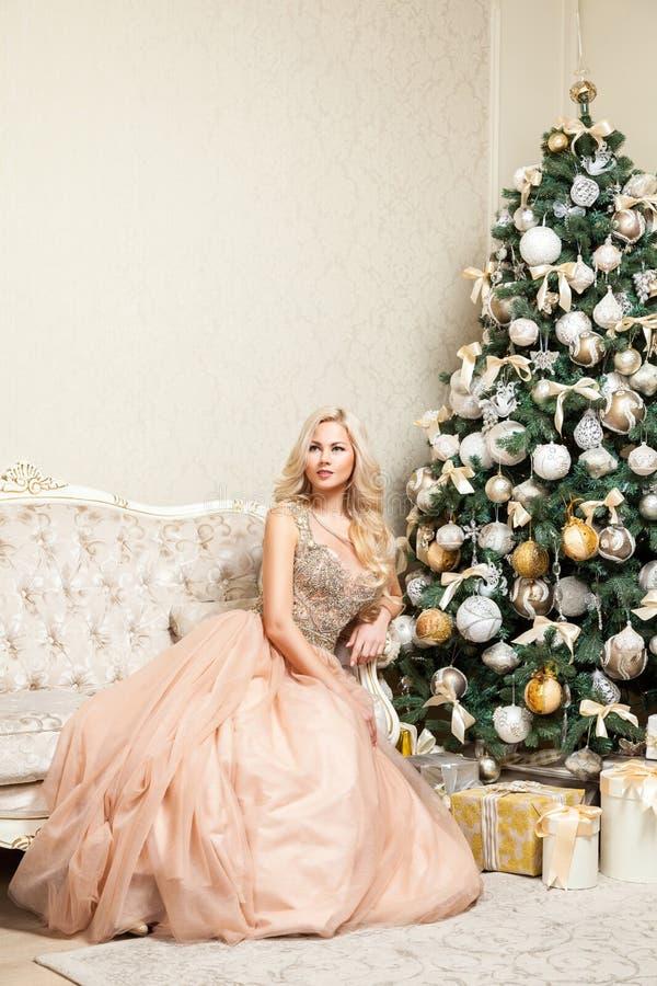Donna bionda graziosa in vestito uguagliante elegante gonfio da bella festa con la posa di seduta dell'acconciatura riccia e di t immagini stock libere da diritti