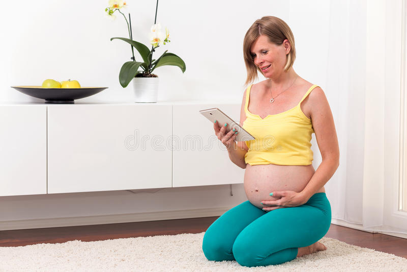 Donna bionda incinta nella casa moderna immagini stock libere da diritti