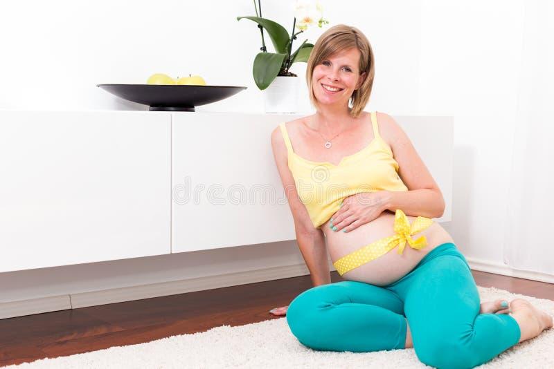 Donna bionda incinta nella casa moderna immagini stock