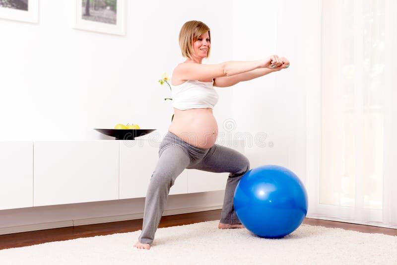 Donna bionda incinta nella sua casa fotografie stock