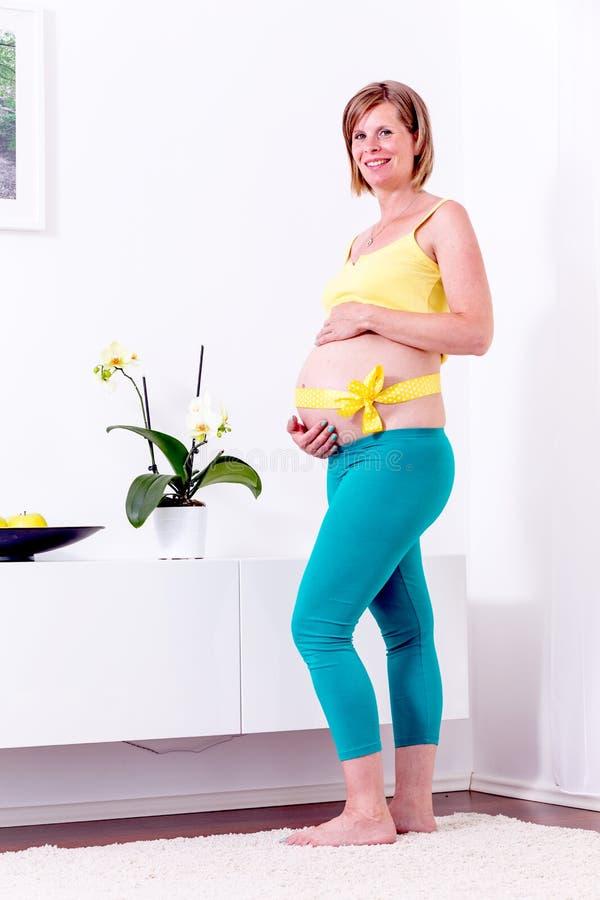 Donna bionda incinta nella sua casa fotografie stock libere da diritti