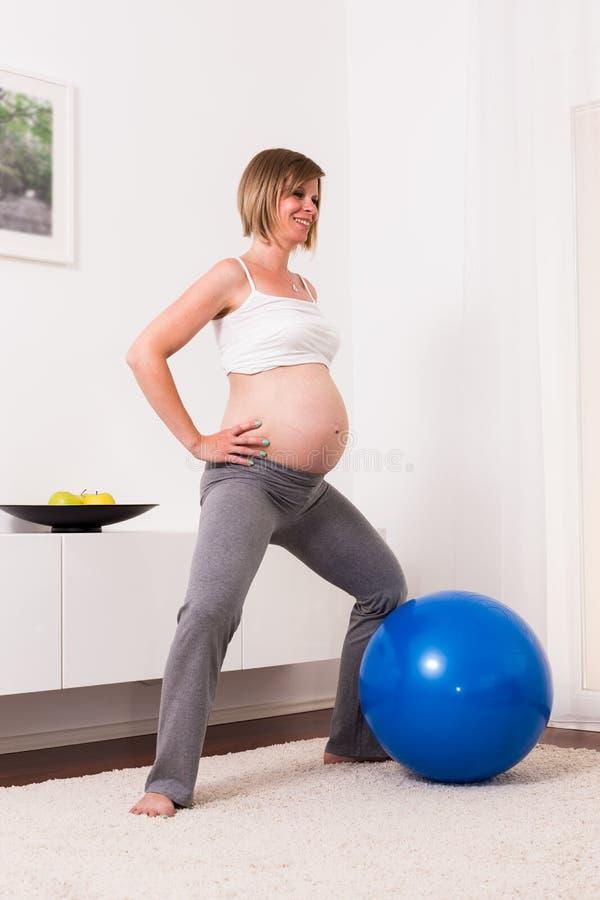 Donna bionda incinta nella sua casa immagini stock