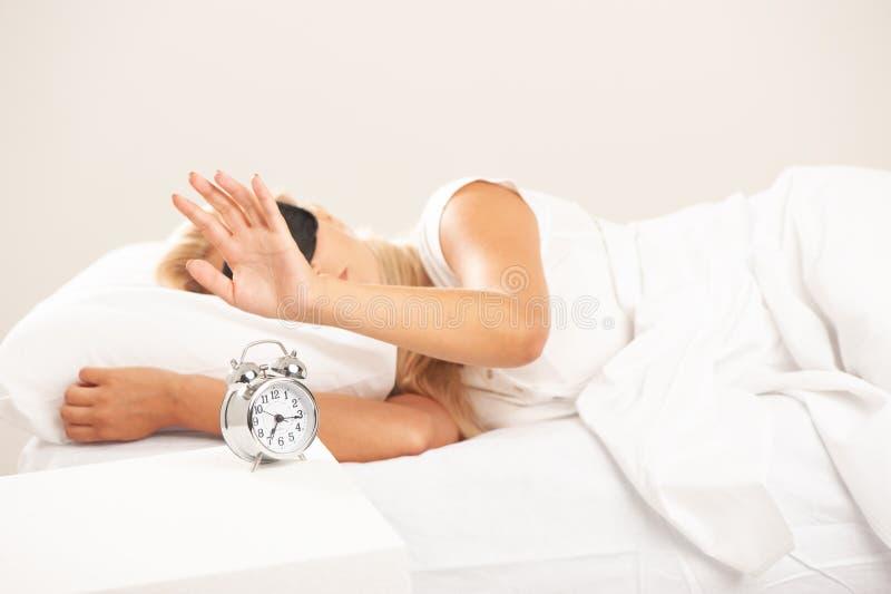 Donna bionda a letto che esamina infastidita la sua sveglia fotografia stock