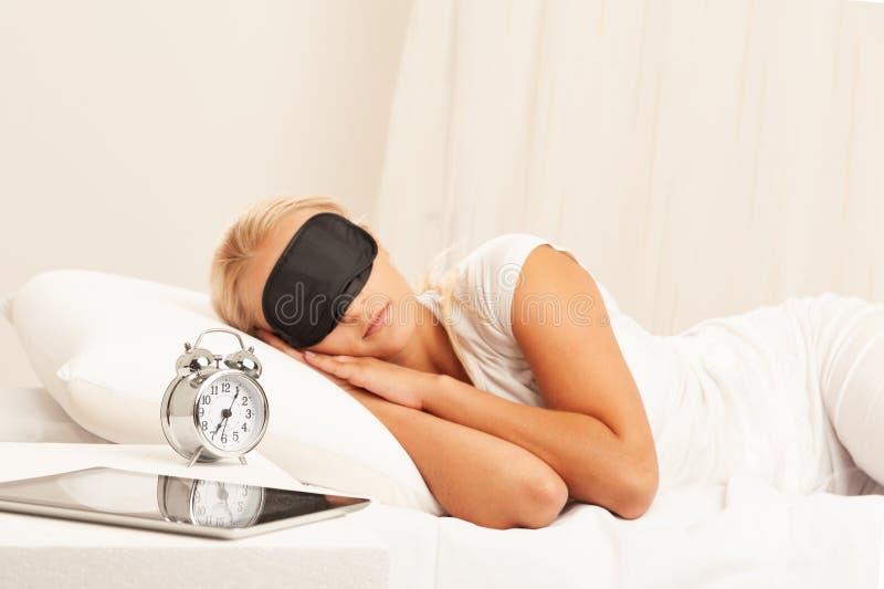 Donna bionda a letto che esamina infastidita la sua sveglia fotografie stock libere da diritti