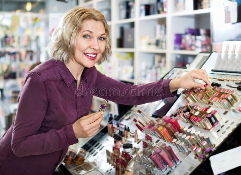 Donna bionda matura che sceglie labbro più grassoccio su esposizione immagini stock