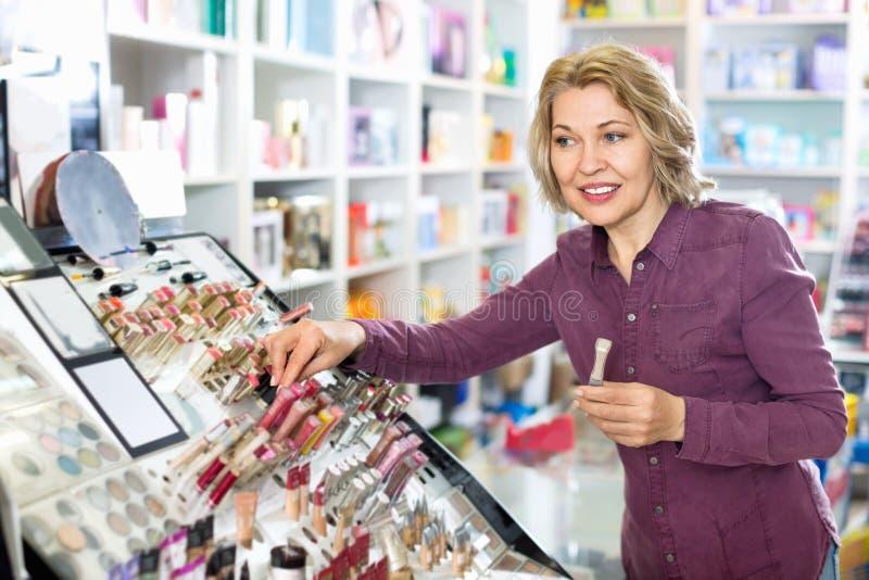 Donna bionda matura che sceglie labbro più grassoccio su esposizione fotografie stock