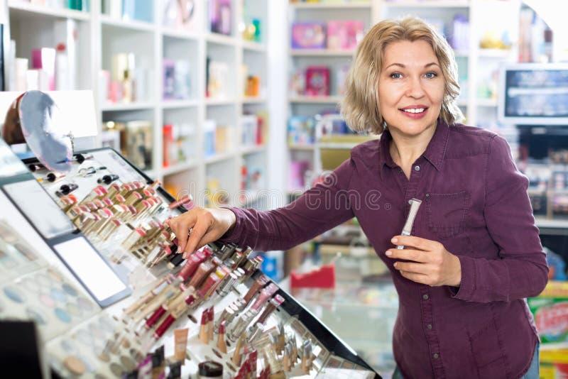 Donna bionda matura positiva che sceglie labbro più grassoccio su esposizione fotografia stock libera da diritti