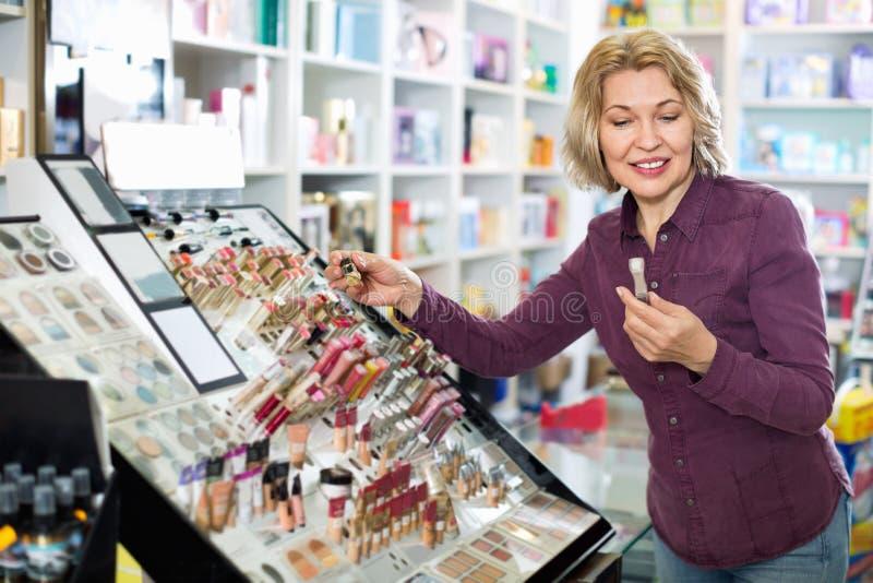 Donna bionda matura positiva che sceglie labbro più grassoccio su esposizione fotografia stock