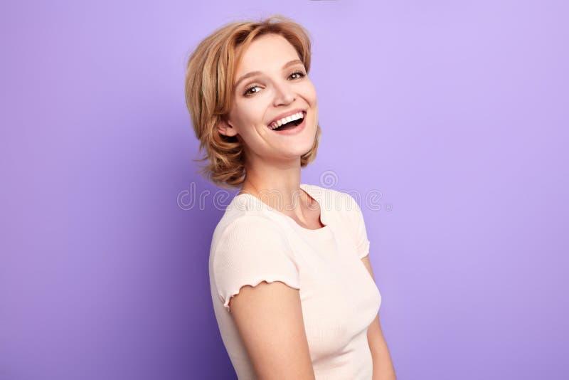 Donna bionda nel fondo bianco alla moda che ride di qualcuno fotografia stock