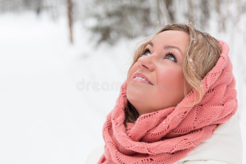 Donna bionda nell'ambito delle precipitazioni nevose fotografie stock libere da diritti